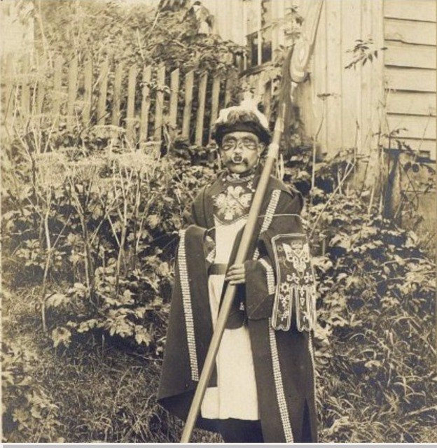 Indian in ceremonial costume with a rod. Territory of Alaska. USA. 1909.